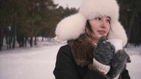 Face of young girl drinking hot coffee outdoors in winter forest