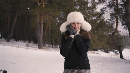 Portrait of young beautiful woman walking in winter forest Stock mozgókép