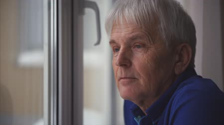 Positive retired man looks at the window while standing near the window at home.