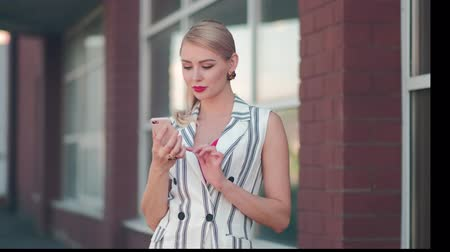 koketa : Beautiful blonde girl in the street next to the building makes a photo on the phone, selfie, business woman laughing and smiling. White suit, red blouse and lips and makeup.