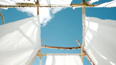 ethereal : White linen cloth on wooden poles swings in the wind. Against the blue sky and green trees and fields.