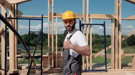 dekarz : Portrait of a male builder in overalls and a yellow helmet on the roof of a frame house.