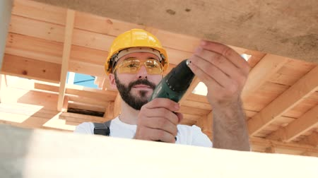 обрамление : Portrait of a male builder in overalls and a yellow helmet on the roof of a frame house. Screws with a screwdriver.