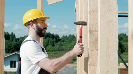 drilling wood : worker roofer builder working on roof structure on construction site Stock Footage