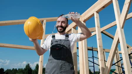 dekarz : The man builder sits on the edge of the roof of the frame house, in a yellow helmet and gray overalls and a white T-shirt. Sweats and pours water on the head from the bottle. Hard work and rest.