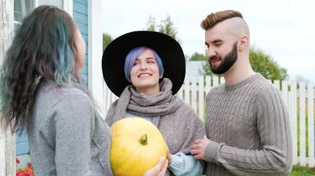 granger : Three people in the background of the village house on the farm speak and laugh. A woman gives a pumpkin as a gift to the family. Working clothes, sweaters and a hat. Good relations of neighbors.