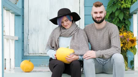 farm house : Portrait of young woman and a man, a family smiling beautiful woman with blue hair sitting on porch of country blue house, green loach plant and vase with sunflowers, yellow pumpkins. A sweater, scarf and hat.