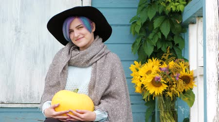 granger : Portrait of young smiling beautiful woman with blue hair sitting on porch of country blue house, green loach plant and vase with sunflowers, yellow pumpkins. A sweater, scarf and hat.