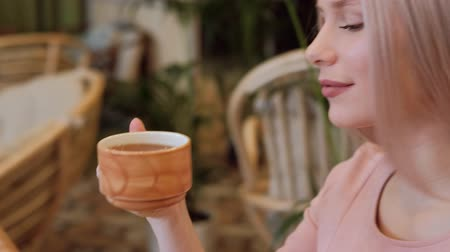business style : Young beautiful blonde woman in a pink dress sitting at a table in a cafe and drinking tea. Rest in a restaurant among green plants. Stock Footage