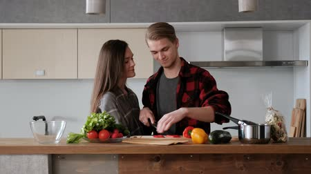 rabanete : Young beautiful couple in plaid shirts are cooking at home in the kitchen. A woman and a man cut vegetables and make a salad of pepper, tomato, radish in a transparent glass dish. Two glasses of wine.