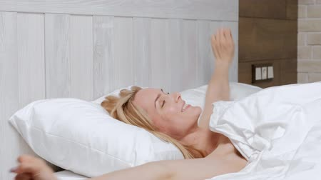 felnőtt : Young attractive middle-aged blonde woman in a white coat wakes up in the morning in bed. Stretches and smiles.