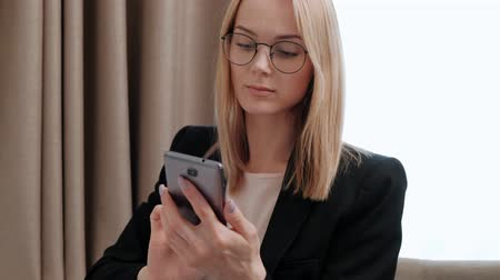 уведомление : Young attractive middle-aged blonde woman in a black business suit and eyeglasses in a hotel room. Writes messages on the smartphone, works and smiles.
