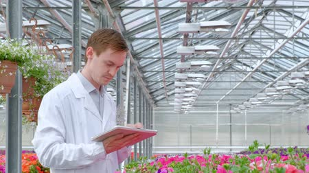 botanikus : A young man in a white coat, a scientist biologist or agronomist examines and analyzes the flowers and green plants in the greenhouse. Writes data to the tablet.
