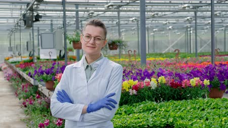 néz : Young beautiful middle-aged woman in glasses, white coat and blue rubber gloves, scientist agronomist, posing against greenhouse with green plants and flowers. Smiles and looks straight into camera.