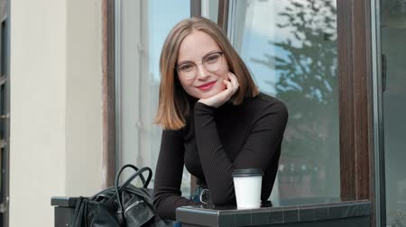 saçlı : Attractive red-haired young woman with short haircut, a four-sided, with glasses and brown turtleneck, is sitting on bench at table in street cafe. Against window background and city street.