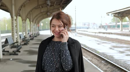 coming home : Attractive middle-aged brunette woman uses a mobile phone at a train station. Waiting for the train.