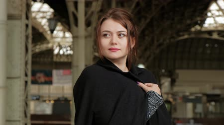 persons : Attractive middle-aged brunette woman in a black coat at the railway station. Waiting for the train. Stock Footage
