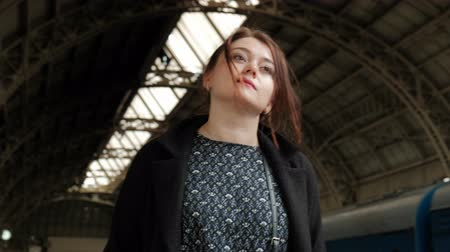 coming home : Attractive middle-aged brunette woman in a black coat at the railway station. Waiting for the train. Stock Footage