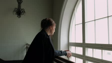 zábradlí : An attractive middle-aged brunette woman in a black coat is leaning on the railing by a large vintage window. Twilight.
