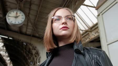 skandinávia : Attractive red-haired young woman with short haircut, wearing glasses and black leather jacket is standing at Vitebsk railway station in St. Petersburg and waiting for train. Big clock. Stock mozgókép