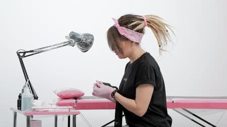 cultura juvenil : Portrait of an attractive female tattoo master. Stylish girl with dreadlocks on a white and pink studio background. She holds a tattoo machine in hands and smiles.