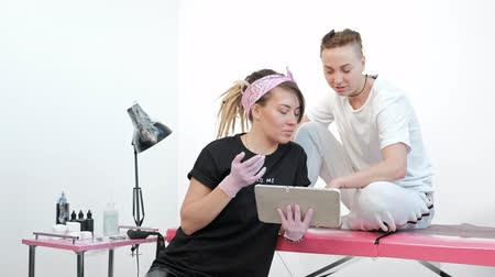 choise : Tattoo master woman discusses sketch with client, shows pictures on tablet in studio. Pink background. Stock Footage
