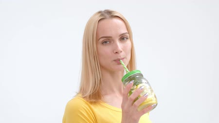 orange t shirt : Attractive young blond woman in a yellow T-shirt and jeans posing on a white background and drinking a fresh cocktail of lemonade from a glass jar with a straw. Studio photography.