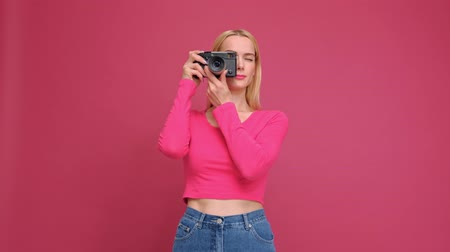 mirrorless : Attractive young woman blonde in a red T-shirt and jeans posing on a pink background. Photographs on a mirrorless camera in retro style and smiling. The concept of the photographer.