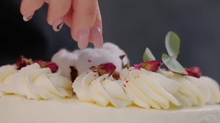 strouhaný : The condater sprinkles the cake with grated almonds and coconut. Close-up of a hand and pouring crumbs. White cake on a gray background. Dostupné videozáznamy