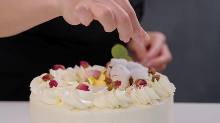 parşömen : The confectioner sprinkles the cake with grated almonds and coconut. Close-up of a hand and pouring crumbs. White cake on a gray background.