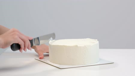 açoitado : White smooth cylindrical cake blank. The confectioner creates the shape of a pastry spatula. Close-up.