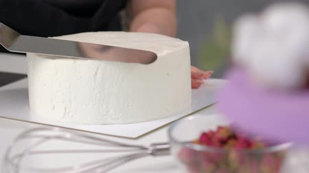 cakes : White smooth cylindrical cake blank. The confectioner creates the shape of a pastry spatula. Close-up.