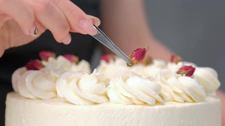 komerční : An attractive young female brunette confectioner decorates a white cake with small red flowers of food rose with tweezers. On a dark gray background.