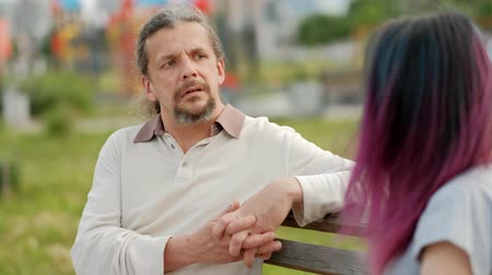 чувствовать : A relaxed attractive middle-aged man with long gray hair and a young woman with dyed hair sitting on a park bench and chatting. Meeting an adult daughter and father. Стоковые видеозаписи