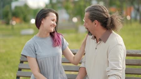 ragaszkodás : A relaxed attractive middle-aged man with long gray hair and a young woman with dyed hair hugging and greeting. Meeting an adult daughter and father.