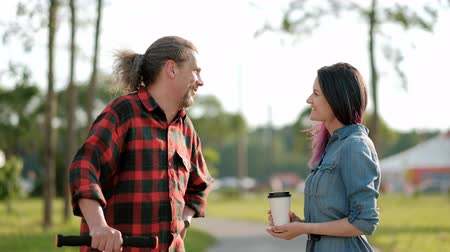 coming home : A relaxed attractive middle-aged man with long gray hair on a kick-scooter and a young woman with dyed hair greet and embrace. Meeting adult daughter and father for a walk in the park. Stock Footage