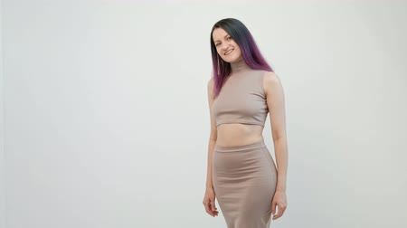 sukně : Attractive young woman with dyed hair in a beige crochet top and skirt posing on a white background. Sexy girl. Dostupné videozáznamy