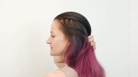 mermaid : Portrait of a young woman on a white background. Long dyed hair. Ombre, color staining. Lilac and blue. Concept work hair stylist. Stock Footage