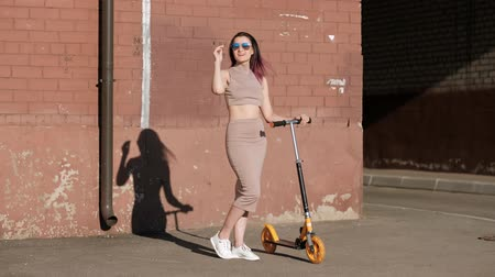 terrakotta : Young beautiful woman in a skirt and sunglasses is riding a kick scooter on the background of a brick wall. Terracotta and brown color of the house. Summer sunny day.