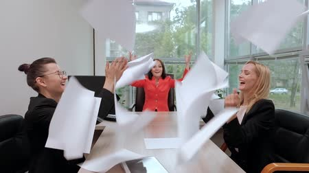 Three beautiful young girls in business suits are sitting at the office desk. Tired of work. Throw paper airplanes, and laugh. Break and rest in the workplace. Wideo