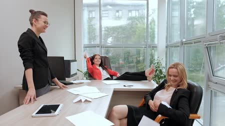 paper airplane : Three beautiful young girls in business suits are sitting at the office desk. Tired of work. Throw paper airplanes, and laugh. Break and rest in the workplace. Stock Footage
