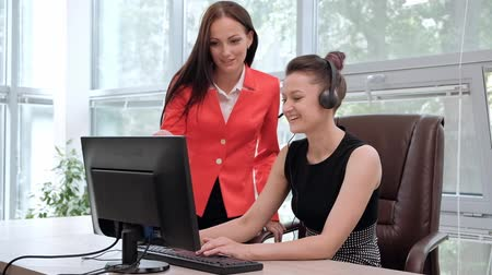 телемаркетинг : Two young women work in a bright office at the computer. Discuss workflows and enjoy a successful deal. Head and subordinate. Customer Support. Стоковые видеозаписи