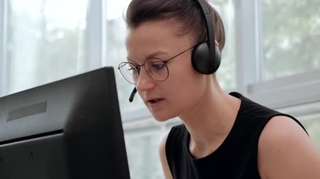 operators : A young attractive woman wearing a black jacket in a black jacket is sitting at her desk in a executive chair. Holds a video conference in headphones with a microphone. Smiles and looks at the monitor. Stock Footage