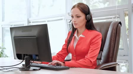 телефон доверия : Young attractive woman in red jacket sitting on desk at head of executive in red jacket. Holds video conference in headphones with microphone. Drinking coffee from white cup. Smiles and communicates.