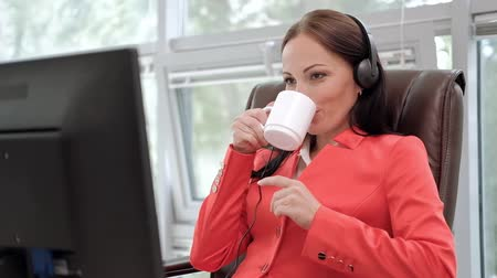 Young attractive woman in red jacket sitting on desk at head of executive in red jacket. Holds video conference in headphones with microphone. Drinking coffee from white cup. Smiles and communicates.