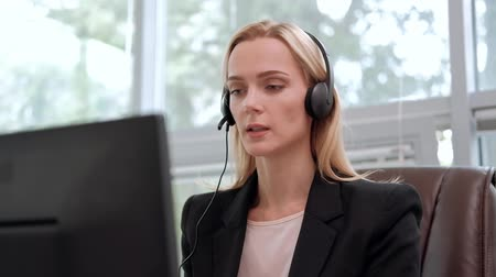 yardım hattı : A young attractive woman wearing a black jacket in a black jacket is sitting at her desk in a executive chair. Holds a video conference in headphones with a microphone. Smiles and looks at the monitor. Stok Video