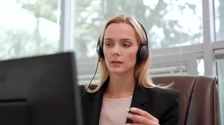 телефон доверия : A young attractive woman wearing a black jacket in a black jacket is sitting at her desk in a executive chair. Holds a video conference in headphones with a microphone. Smiles and looks at the monitor. Стоковые видеозаписи