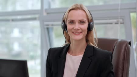 A young attractive woman wearing a black jacket in a black jacket is sitting at her desk in a executive chair. Holds a video conference in headphones with a microphone. Smiles and looks at the monitor. Wideo