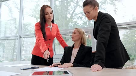 brifing : Three young attractive women in business suits are sitting at a desk and discussing workflows. Head and subordinates. Working team of professionals and colleagues. Feminism and feminine power. Stok Video