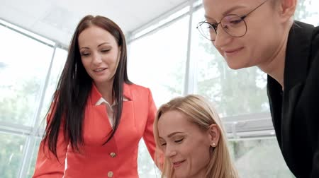 Three young attractive women in business suits are sitting at a desk and discussing workflows. Head and subordinates. Working team of professionals and colleagues. Feminism and feminine power. Wideo